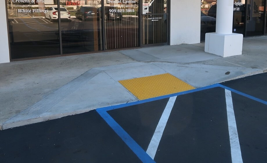 ADA curb ramp with handicap parking compliant markings